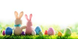Dois coelhos com os ovos decorados isolados em Sunny Meadow foto de stock