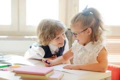 Dois colega, laddie e girlie pequenos, estão sentando-se na mesma mesa imagens de stock