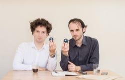 Dois colegas caucasianos novos que sentam-se na tabela, guardando bolas de Yin Yang do chinês no escritório com fundo claro fotografia de stock