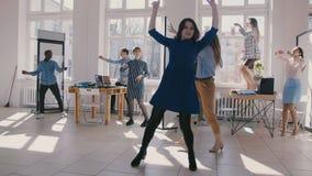 Dois colegas de escritório fêmeas do divertimento novo que dançam junto com o pessoal multi-étnico da empresa que comemora o  video estoque