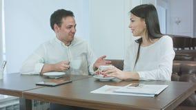 Dois colegas de trabalho alegres que falam sobre o café em um café vídeos de arquivo