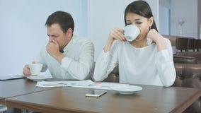 Dois colegas de trabalho que não sentem chá quente bom e bebendo durante o almoço em um café foto de stock