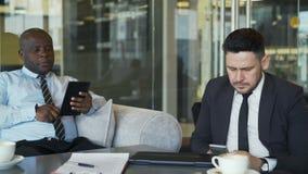 Dois colegas do negócio no vestuário formal que senta e que usa seus smartphone e tabuleta no café vítreo durante a reunião video estoque