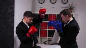Dois colegas dos concorrentes que encaixotam no escritório do centro de negócio video estoque