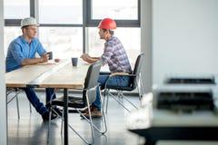 Dois colegas estão tendo um diálogo ao descansar no escritório imagem de stock royalty free
