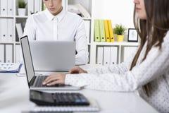 Dois colegas fêmeas estão trabalhando em um escritório branco em seu regaço Imagens de Stock