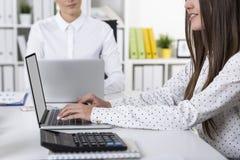 Dois colegas fêmeas estão trabalhando em um escritório branco em seu regaço Fotografia de Stock