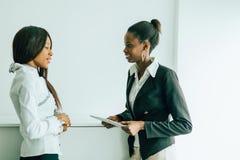 Dois colegas que falam sobre os índices em um PC da tabuleta no nos Foto de Stock