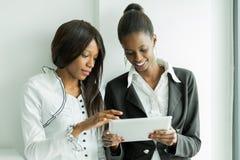 Dois colegas que falam sobre os índices em um PC da tabuleta no nos Fotos de Stock