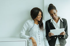 Dois colegas que falam sobre os índices em um PC da tabuleta no nos Fotos de Stock Royalty Free