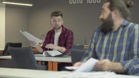 Dois colegas que sentam-se no escritório que estuda a informação de trabalho nova dos papéis Homem novo no fundo que pede o conse vídeos de arquivo