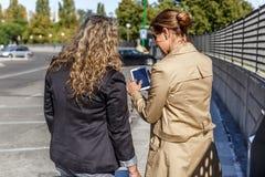 Dois colegas reveem algo em um dispositivo móvel, ao andar fotografia de stock royalty free