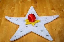 Dois coloriram estrelas e uma bola vermelha do Natal no centro Foto de Stock