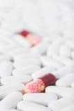 Dois comprimidos vermelhos em muitos comprimidos brancos Fotos de Stock Royalty Free