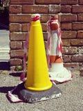 Dois cones do tráfego na frente da parede de tijolo Fotos de Stock
