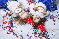 Dois confetes coloridos da forma da criança das meninas no assoalho Imagens de Stock
