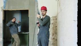 Dois construtores alegres com um perfurador em uma mão vídeos de arquivo
