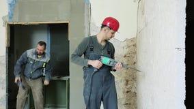 Dois construtores alegres com um perfurador em uma mão filme