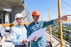 Dois construtores no canteiro de obras que olha a reunião do contratante dos planos com homem de negócio imagens de stock