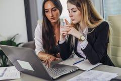 Dois contadores fêmeas que trabalham junto no relatório financeiro usando o portátil que senta-se na mesa no departamento de cont foto de stock royalty free