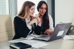 Dois contadores fêmeas que trabalham junto no relatório financeiro usando o portátil que senta-se na mesa no departamento de cont imagens de stock