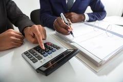 Dois contadores que calculam a fatura do imposto usando a calculadora fotografia de stock royalty free