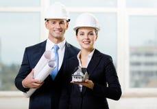 Dois contratantes que mantêm modelos e a casa modelo Imagem de Stock