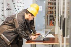 Dois coordenadores da manutenção inspecionam o sistema de proteção do relé com l fotos de stock