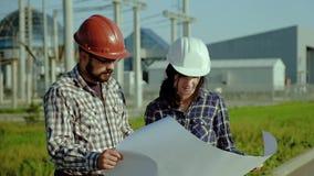 Dois coordenadores discutem aprovam o plano no pedaço de papel grande A planta está no fundo Movimento lento video estoque