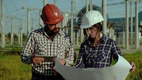 Dois coordenadores discutem para aprovar o plano no pedaço de papel grande, fazendo algumas marcas A planta está no fundo Movimen filme