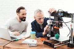 Dois coordenadores imprimem os detalhes na impressora 3d Um homem das pessoas idosas controla o processo Imagens de Stock