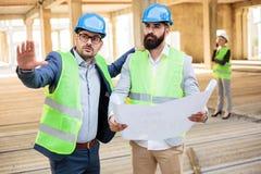Dois coordenadores masculinos novos que discutem detalhes do projeto em um canteiro de obras foto de stock
