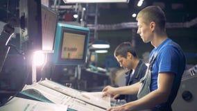 Dois coordenadores que trabalham com equipamento automatizado industrial usando o écran sensível filme