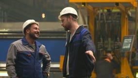 Dois coordenadores sorriem, riem e agitam as mãos na fábrica da indústria pesada filme