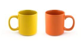 Dois copos amarelos e alaranjados vazios grandes isolados no fim do branco acima Imagens de Stock