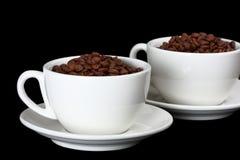 Dois copos brancos, cheios de feijões de café Fotos de Stock