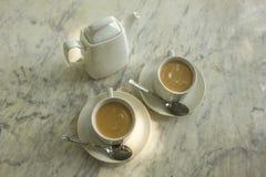 Dois copos brancos com chá do leite, colheres e um bule cerâmico na superfície de mármore do close-up da tabela fotos de stock royalty free