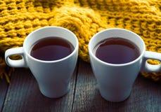 Dois copos brancos do chá e do lenço na mesa de madeira velha Imagens de Stock Royalty Free