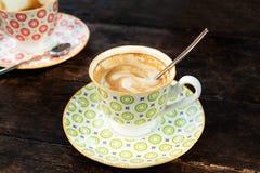 Dois copos coloridos com cappuccino quente em uma tabela de madeira Imagem de Stock Royalty Free