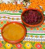 Dois copos com as bagas de doce do mel e de framboesa e de espinheiro cerval do mar na toalha de mesa colorida foto de stock