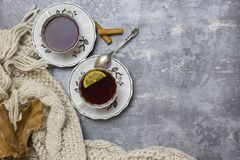 Dois copos com chá preto e limão e pires, limão, varas de canela, colher, folhas do carvalho e lenço feito malha próximo, no back imagens de stock