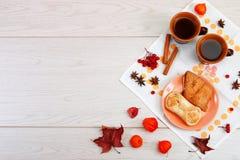 Dois copos da argila marrom com chá estão em um guardanapo de linho branco As cookies de manteiga com doce e bolo do fruto com re imagem de stock