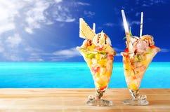 Dois copos da salada de fruto com o mar no fundo imagens de stock