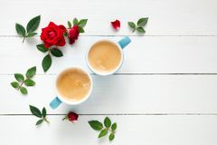Dois copos de café do café e rosas do vermelho florescem no fundo branco Fotografia de Stock Royalty Free