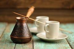 Dois copos de café e cezve de cobre com café preto fresco em velho Imagens de Stock