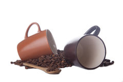 Dois copos de café e feijões de café no branco Fotos de Stock Royalty Free