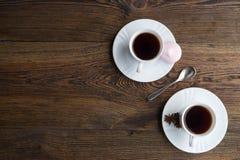 Dois copos de café na tabela de madeira escura Imagens de Stock Royalty Free