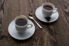 Dois copos de café na tabela de madeira escura Fotografia de Stock