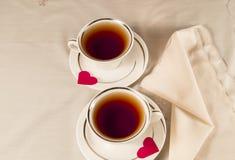 Dois copos de chá brancos em uns pires com corações vermelhos Fotos de Stock