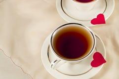 Dois copos de chá brancos em uns pires com corações vermelhos Imagem de Stock Royalty Free